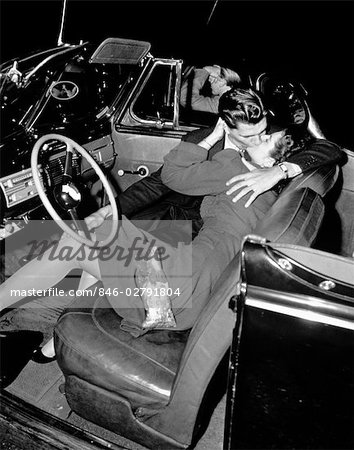 1940s 1950s COUPLE MAN AND WOMAN KISSING IN FRONT SEAT OF CONVERTIBLE CAR AT DRIVE-IN Stock Photo - Rights-Managed, Image code: 846-02791804