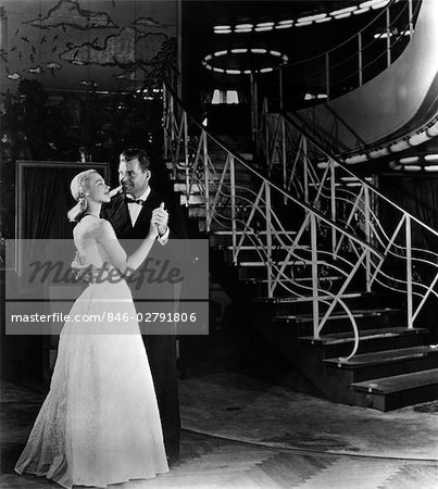 1940s ROMANTIC COUPLE MAN AND WOMAN FORMALLY DRESSED DANCING NEAR ART DECO STAIRCASE