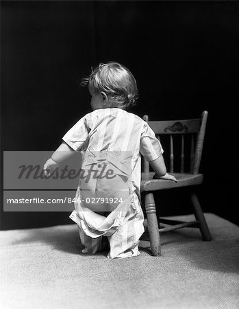 1940s BABY WEARING DROP SEAT PAJAMAS SHOWING BARE BOTTOM LEANING ON CHAIR Stock Photo - Rights-Managed, Image code: 846-02791924