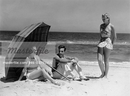 1930s TWO WOMEN 1 MAN SITTING UNDER BEACH UMBRELLA WEARING FASHIONABLE SWIMWEAR Stock Photo - Rights-Managed, Image code: 846-02791956