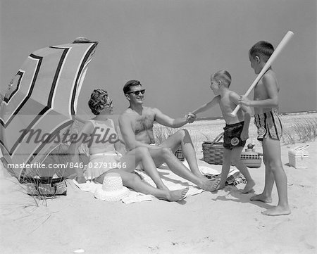 1960s AT THE BEACH TWO BOYS WITH BASEBALL BAT TRYING TO PULL UP FATHER SEATED NEXT TO MOTHER SO HE WILL PLAY WITH THEM Stock Photo - Rights-Managed, Image code: 846-02791966