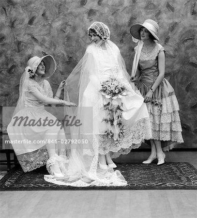 1900 1910s BRIDE WITH ONE BRIDESMAID ON EITHER SIDE HELPING FIX HER WEDDING DRESS Stock Photo - Rights-Managed, Image code: 846-02792050