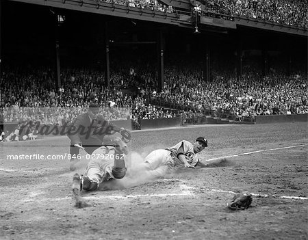1950s PROFESSIONAL MAJOR LEAGUE BASEBALL GAME RUNNER SLIDING INTO HOME BASE AS UMPIRE SIGNALS SAFE Stock Photo - Rights-Managed, Image code: 846-02792062