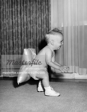 1950s LAUGHING BABY IN DIAPER AND SHOES LEARNING TO WALK WITH A PILLOW TIED TO HIS REAR END Stock Photo - Rights-Managed, Image code: 846-02792105