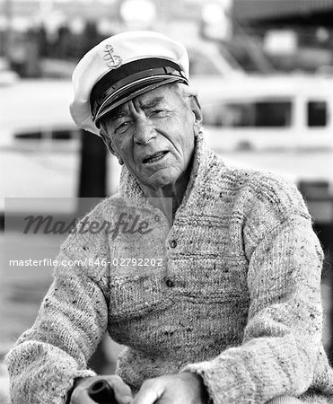 1970s OLDER MAN IN FISHERMAN'S HAT SWEATER HOLDING PIPE SITTING ON DOCKS OUTDOOR Stock Photo - Rights-Managed, Image code: 846-02792202