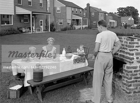 1950s FAMILY IN BACKYARD COOKING HAMBURGERS