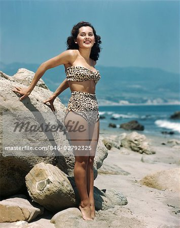 1940s BRUNETTE WOMAN LEOPARD SKIN TWO PIECE BATHING SUIT STANDING ON ROCKY BEACH Stock Photo - Rights-Managed, Image code: 846-02792325