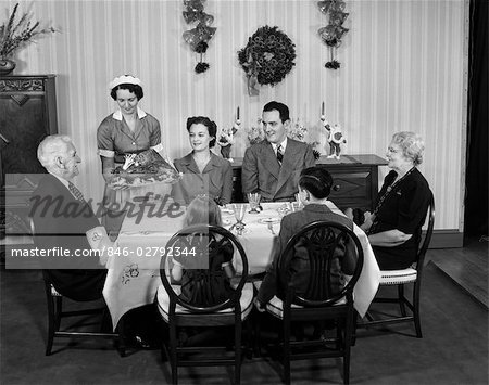 1940s TWO GENERATION FAMILY IN DINING ROOM BEING SERVED CHRISTMAS TURKEY BY MAID Stock Photo - Rights-Managed, Image code: 846-02792344
