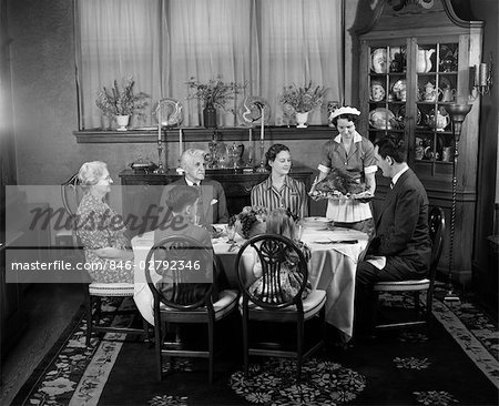 1940s TWO GENERATION FAMILY IN DINING ROOM THANKSGIVING TURKEY BEING SERVED BY MAID Stock Photo - Rights-Managed, Image code: 846-02792346