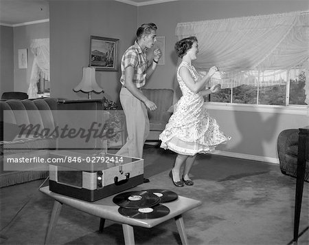 1950s LAUGHING TEENAGE COUPLE DANCING TO THE PHONOGRAPH PLAYING 78 RPM RECORDS IN LIVING ROOM Stock Photo - Rights-Managed, Image code: 846-02792414