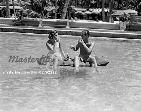1930s 1940s COUPLE DRINKING WHILE FLOATING IN A POOL ON A RUBBER RAFT AT FLORIDA RESORT Stock Photo - Rights-Managed, Image code: 846-02792922