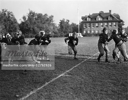 1930s BOYS SCHOOL FOOTBALL TEAM BOY RUNNING WITH BALL CENTER Stock Photo - Rights-Managed, Image code: 846-02792926