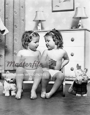 1950s TWIN GIRLS SITTING IN A DOUBLE SEAT WEARING PANTIES ONLY WHILE EATING GRAHAM CRACKERS Stock Photo - Rights-Managed, Image code: 846-02792931