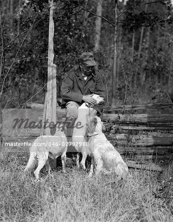 1920s ELDERLY MAN SITTING WITH RIFLE RESTING AGAINST FENCE PETTING ONE OF THREE HUNTING DOGS Stock Photo - Rights-Managed, Image code: 846-02792988