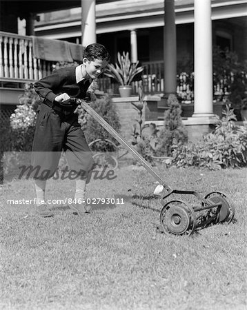 1930s 1940s BOY PUSHING LAWN MOWER WEAR KNICKERS CUTTING THE GRASS CHORE SUMMER JOB YARD WORK Stock Photo - Rights-Managed, Image code: 846-02793011