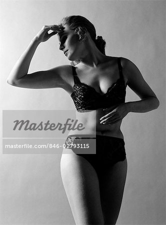1970s WOMAN WEARING BLACK LACE BRA AND PANTIES HEAD TURNED TO SIDE HAND TOUCHING FOREHEAD ARMS IN GRACEFUL POSE INDOOR Stock Photo - Rights-Managed, Image code: 846-02793115