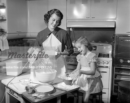 1950s MOTHER & DAUGHTER BAKING A CAKE