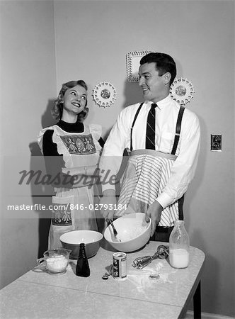 1950s COUPLE HUSBAND WIFE KITCHEN TABLE BOTH WEAR APRON MAN MIXING SPOON BOWL BLENDING INGREDIENTS WOMAN ARMS FOLDED SMILING UP AT MAN SATISFIED AMUSED