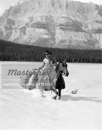 1930s COWBOY WITH BATWING CHAPS ON A BAY HORSE CROSSING A RIVER LEADING A PAINT PACK HORSE WITH MOUNTAINS IN BACKGROUND
