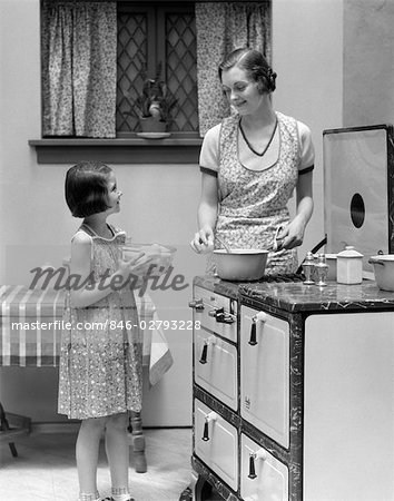 1920s YOUNG GIRL HELPING MOTHER COOK IN HOME KITCHEN INDOOR