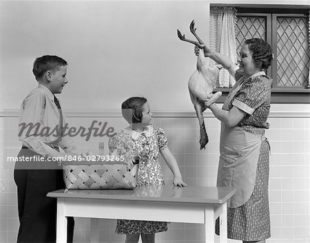 1940s HOUSEWIFE SHOWING RAW FRESH PLUCKED TURKEY TO SON AND DAUGHTER IN KITCHEN Stock Photo - Rights-Managed, Image code: 846-02793265