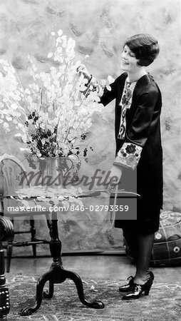 1920s WOMAN MAKING FLOWER ARRANGEMENT STANDING BY CHIPPENDALE TABLE ON ORIENTAL CARPET
