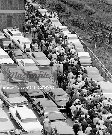 1960s OVERHEAD OF FACTORY WORKERS IN CROWDED PARKING LOT GETTING OUT OF CARS & WALKING TOWARD BUILDING TO WORK Stock Photo - Rights-Managed, Image code: 846-02793400