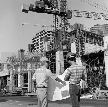 1980s REAR VIEW OF TWO HARD HAT WORKERS STANDING IN FRONT OF MAJOR CONSTRUCTION SITE LOOKING OVER BUILDING PLANS MEN OUTDOOR Stock Photo - Rights-Managed, Image code: 846-02793439
