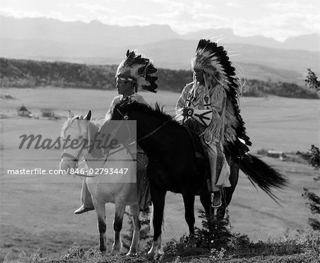 1930s PAIR OF SIOUX INDIANS WEARING HEADDRESSES ON HORSEBACK Stock Photo - Rights-Managed, Image code: 846-02793447