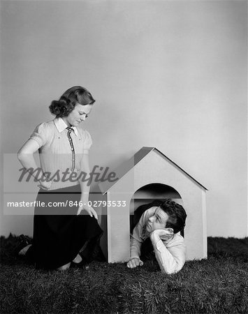 1940s YOUNG TEEN COUPLE ARGUMENT GIRL FROWNING BOY LYING IN DOGHOUSE DOG HOUSE Stock Photo - Rights-Managed, Image code: 846-02793533