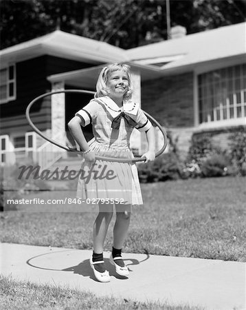 1950s GIRL IN DRESS ON SUBURBAN SIDEWALK USING THE HULA HOOP Stock Photo - Rights-Managed, Image code: 846-02793552