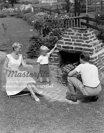 1940s 1950s FAMILY IN BACKYARD COOKING HAMBURGERS ON BRICK BARBEQUE