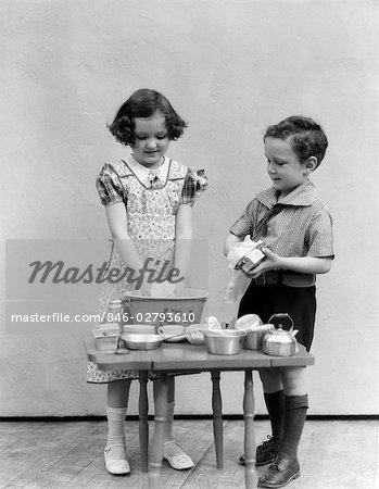 1930s 1940s GIRL WASHING TOY DISHES SMALL BASIN BOY DRYING DISH TOYS TEA SET CHORES HOUSEHOLD PLAYING HOUSE Stock Photo - Rights-Managed, Image code: 846-02793610