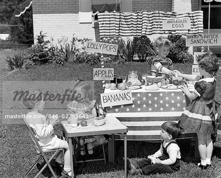 1950s KIDS IN BACKYARD PLAYING STORE WITH SIGNS SELLING APPLES BANANAS SANDWICHES LOLLYPOPS Stock Photo - Rights-Managed, Image code: 846-02793641