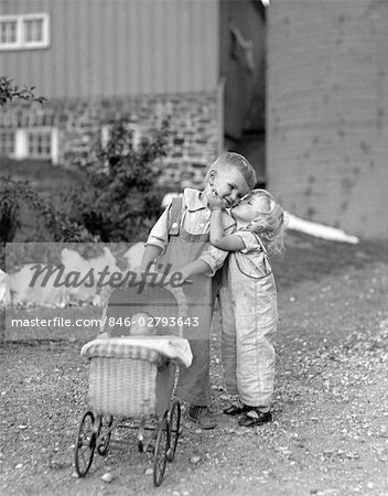 1930s 1940s LITTLE GIRL KISSING BOY PUSHING TOY BABY CARRIAGE IN FRONT OF BARN Stock Photo - Rights-Managed, Image code: 846-02793643