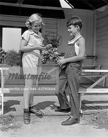 1940s BOY WEARING OVERALLS GIVING GIRL BOUQUET FLOWERS AT FARM STAND Stock Photo - Rights-Managed, Image code: 846-02793664
