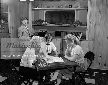 1950s GIRLS PLAYING SCRABBLE IN REC ROOM WITH BOY CHANGING RECORDS Stock Photo - Rights-Managed, Image code: 846-02793709