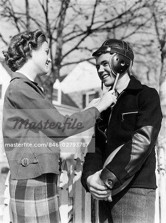 1940s CUTE ROMANTIC TEEN COUPLE GIRL HOLDING STRAPS OF BOYS FOOTBALL HELMET