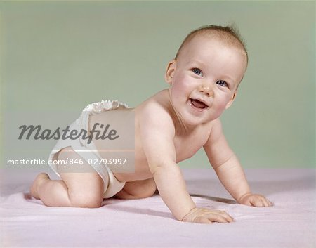 1960s SMILING BABY WEARING DIAPER CRAWLING ON BLANKET