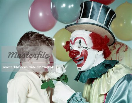 1950s BOY SMILING SMELL SMELLING WHITE ROSE FROM CIRCUS CLOWN TOP HAT RED NOSE BIG SMILE BALLOONS BACKGROUND Stock Photo - Rights-Managed, Image code: 846-02794094