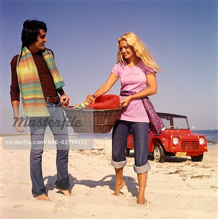 1970s COUPLE BEACH CARRY PICNIC BASKET RED DUNE BUGGY IN BACKGROUND Stock Photo - Rights-Managed, Image code: 846-02794131