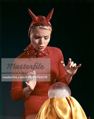 1960s BLOND WOMAN IN RED DEVIL COSTUME WITH HORNS LOOKING SURPRISED AT A CRYSTAL BALL Stock Photo - Rights-Managed, Image code: 846-02794278