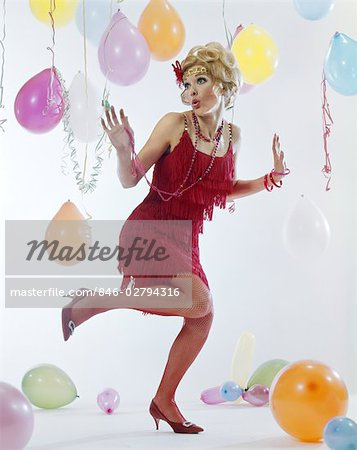 1970s WOMAN RED FRINGE 1920s FLAPPER DRESS DANCING CHARLESTON AMONG PARTY BALLOONS STREAMERS Stock Photo - Rights-Managed, Image code: 846-02794316