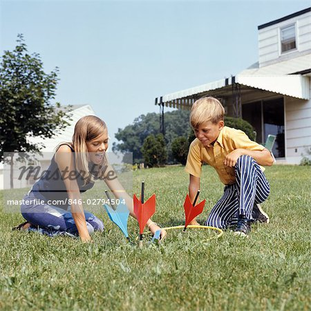 1970s BOY GIRL PLAYING LAWN DARTS GAME IN BACKYARD Stock Photo - Rights-Managed, Image code: 846-02794504