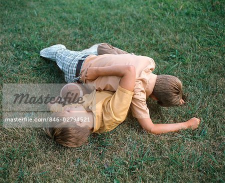 TWO BOYS WRESTLING PLAYING FOOTBALL TACKLE ON LAWN Stock Photo - Rights-Managed, Image code: 846-02794521