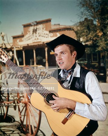 1960s MAN PLAYING ACOUSTIC GUITAR COWBOY SALOON IN BACKGROUND Stock Photo - Rights-Managed, Image code: 846-02794691