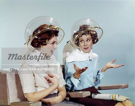 1960s TWO WOMEN SITTING UNDER BEAUTY SALON HAIR DRYER HOODS IN CURLERS TALKING GOSSIP Stock Photo - Rights-Managed, Image code: 846-02795136