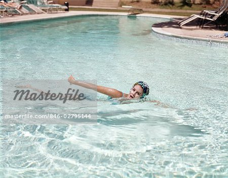 1960s WOMAN BLUE BATHING CAP SWIMMING IN WATER POOL OVERHAND STROKE Stock Photo - Rights-Managed, Image code: 846-02795144