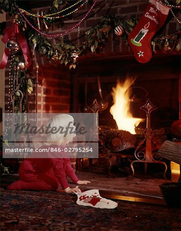 1960s SMALL BLOND GIRL AT FIREPLACE DECORATED FOR CHRISTMAS HOLDING STOCKING LOOKING FOR SANTA CLAUS Stock Photo - Rights-Managed, Image code: 846-02795254