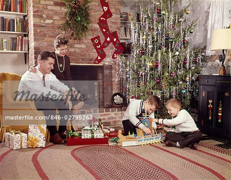 1960s FAMILY IN LIVING ROOM CHRISTMAS TREE BOYS PLAYING WITH TOYS MOTHER FATHER SITTING IN CHAIR Stock Photo - Rights-Managed, Image code: 846-02795263
